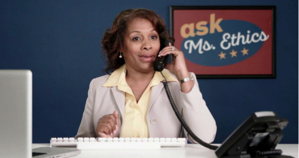 Photo of a woman on the phone in front of an Ask Ms. Ethics poster